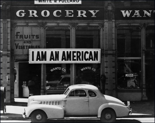 "A large sign reading ""I am an American"" placed in the window of a store"